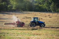Hay baler in the field. Hay baler and hay bales in the field royalty free stock image