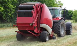 Hay baler machine pulled by a red tractor on a freshly cut field.  stock images