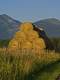 Hay Bales. This image of the hay bales piled high with the mountains in the background was taken in the early evening in western MT Stock Photography