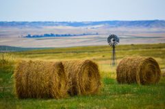 Hay Bales em um campo com moinho de vento Imagem de Stock