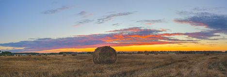 Hay bales on the field after harvesting on a background of setting sun and colorful sunset sky. stock images