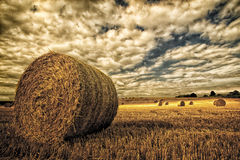 Hay Bales In Field Under An Angry Sky Stock Photo