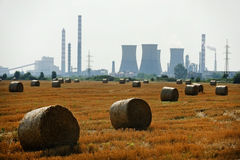 Hay bales with petrochemical plant on background Royalty Free Stock Photo