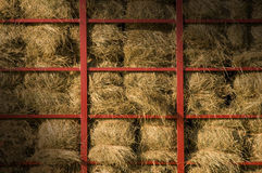 Hay bales piled within a cart lit diagonally Royalty Free Stock Images