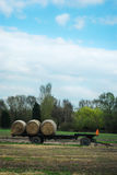 Hay bales trailer in field. Hay bales trailer in a field. Blue cloudy sky royalty free stock photos