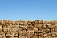 Hay bales wall against blue sky. A wall of hay bales against a blue sky Stock Image