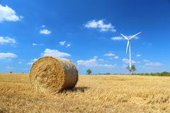 Hay bales and wind turbine. In the background with blue sky and small clouds Stock Photos