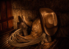 Hay and Boots. Cowboy Hat, Cowboy Boots, and other Cowboy Gear Stacked Together in Hay Loft royalty free stock images