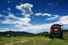 Hay bundles and tractor Royalty Free Stock Photography