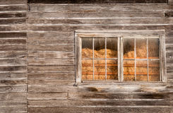 Hay Through the Dirty Barn Window Royalty Free Stock Photography