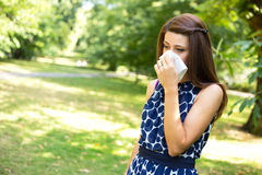Hay fever. Young woman with hay fever blowing her nose Royalty Free Stock Image
