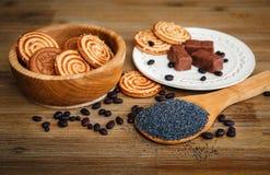 Hay galletas, caramelo, guisantes del chocolate, amapola; Placa de cerámica; Comida dulce sabrosa en el fondo de madera Imagenes de archivo