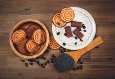 Hay galletas, caramelo, guisantes del chocolate, amapola; Platillo de la porcelana, comida dulce sabrosa en el fondo de madera, v Imagen de archivo