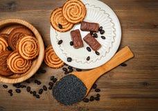 Hay galletas, caramelo, guisantes del chocolate, amapola; Platillo de la porcelana, comida dulce sabrosa en el fondo de madera, v Imagen de archivo libre de regalías