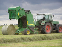 Hay gathering 6. The unit for hay gathering  in rolls. In a photo the moment is represented when the roll is rolled out from the open bunker Royalty Free Stock Photo