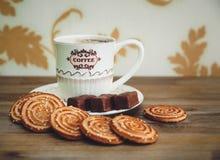 Hay las galletas, el caramelo de chocolate, el platillo y el casquillo con Coffe, comida dulce sabrosa de la porcelana en el fond Fotos de archivo libres de regalías