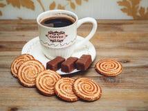 Hay las galletas, el caramelo de chocolate, el platillo y el casquillo con Coffe, comida dulce sabrosa de la porcelana en el fond Imagen de archivo