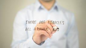 Hay milagros todo alrededor de usted, escritura del hombre en la pantalla transparente imagen de archivo