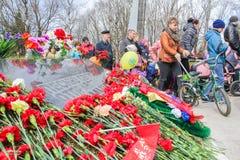 Hay muchas flores rojas en la placa conmemorativa Fotografía de archivo
