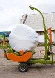 Hay packing machine. Machine for packing hay into synthetic cover royalty free stock photography