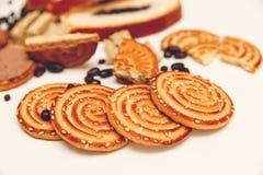 Hay pedazos de rollo con la semilla de amapola, galletas, Halavah, guisantes del chocolate, comida dulce sabrosa en el Background Imagen de archivo