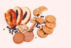 Hay pedazos de rollo con la semilla de amapola, galletas, Halavah, guisantes del chocolate, comida dulce sabrosa en el fondo blan Imagen de archivo libre de regalías