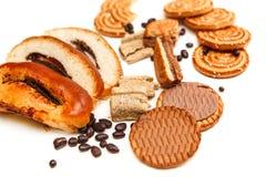 Hay pedazos de rollo con la semilla de amapola, galletas, Halavah, guisantes del chocolate, comida dulce sabrosa en el fondo blan Fotografía de archivo