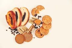 Hay pedazos de rollo con la semilla de amapola, galletas, Halavah, guisantes del chocolate, comida dulce sabrosa en el fondo blan Imagen de archivo