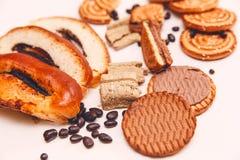 Hay pedazos de rollo con la semilla de amapola, galletas, Halavah, guisantes del chocolate, comida dulce sabrosa en el fondo blan Foto de archivo libre de regalías