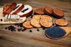 Hay pedazos de rollo con la semilla de amapola, galletas, Halavah, guisantes del chocolate, comida dulce sabrosa en el fondo de m Fotografía de archivo libre de regalías