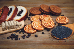 Hay pedazos de rollo con la semilla de amapola, galletas, Halavah, guisantes del chocolate, comida dulce sabrosa en el fondo de m Fotos de archivo
