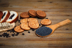 Hay pedazos de rollo con Poppy Seed, galletas, Halavah, guisantes del chocolate, comida dulce en el fondo de madera Fotos de archivo