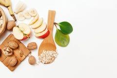 Hay plátano, Aple, anaranjados con las nueces en la placa de madera y la avena rodada, cuchara de madera, trébede, con las hojas  Imagen de archivo libre de regalías