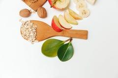 Hay plátano, Aple, anaranjados con las nueces en la placa de madera y la avena rodada, cuchara de madera, trébede, con las hojas  Fotografía de archivo libre de regalías