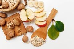 Hay plátano, Apple, anaranjados con las nueces en la placa de madera y la avena rodada, cuchara de madera, trébede, con las hojas Imágenes de archivo libres de regalías