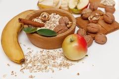 Hay plátano, Apple, anaranjados con las nueces en la placa de madera y la avena rodada, cuchara de madera, trébede, con las hojas Imagenes de archivo
