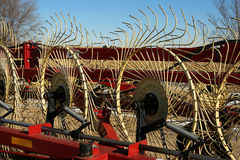 Hay Rake. Folded up red hay rake with pale yellow tines on a bright winter day stock photos