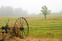 Hay rake in field in fog. A view of an old fashioned hay rake in a country hayfield in morning fog Stock Photography
