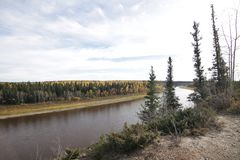 Hay River. As it winds its way through an autumn forest. There is a light speckling of golden leaves spread throughout the evergreen forest on the far side of stock images