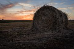 Hay roll in a meadow in front of colorful sunset sky. royalty free stock images