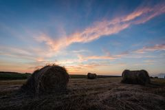 Hay rolls in a meadow in front of colorful sunset sky. royalty free stock photography