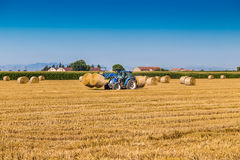 Hay round bales lift by farm tractor Stock Photos