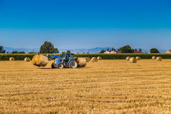 Hay round bales lift by farm tractor Stock Images