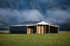 Hay shed. A shed with rolls of hay on a meadow Royalty Free Stock Photos