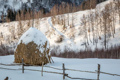 Hay stack covered in snow. At sunset and a man walking alone Stock Images