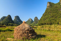 Hay stack on the land in a rocky hill landscape Stock Photos