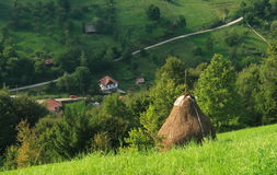 Hay stack on rural hillside. Scenic view of hay stack on green hillside with village in valley, Bran, Romania Royalty Free Stock Image