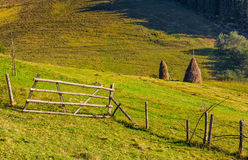 Hay stacks behind the fence on rural field. Lovely Carpathian countryside landscape in early autumn morning Stock Photos