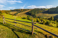 Hay stacks behind the fence on rural field. Lovely Carpathian hilly countryside landscape near forest in early autumn morning Stock Photography