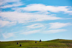 Hay stacks on hillside under the beautiful sky. Hay stacks on grassy hills under the beautiful cloudy blue sky. lovely Carpathian countryside landscape in early Stock Photos